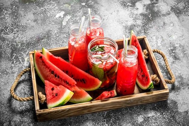 Wassermelonencocktail auf holztablett auf rustikalem tisch.