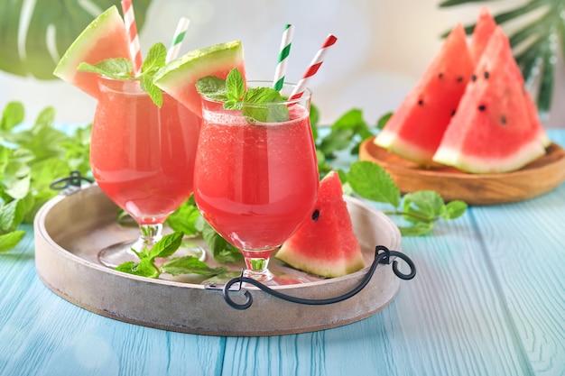 Wassermelonencocktail mit minze und eis. sommer erfrischende getränke in gläsern auf blauem holztisch. konzept der gesunden sommerernährung.