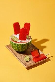 Wassermeloneneis am stiel auf holztablett über gelb
