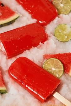 Wassermeloneneis am stiel und geschnittene zitrone auf eiswürfelschale