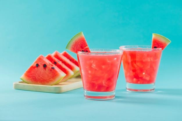 Wassermelonengetränk in gläsern mit wassermelonenscheiben im sommer
