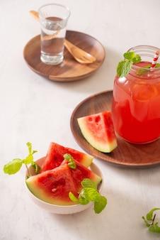 Wassermelonengetränk in glas mit wassermelonenscheiben auf weißer oberfläche