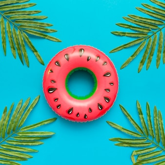 Wassermelonenpoolfloss mit tropischen blattpalmen