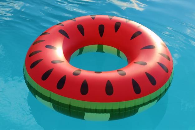 Wassermelonenring im blauen wasser des pools.
