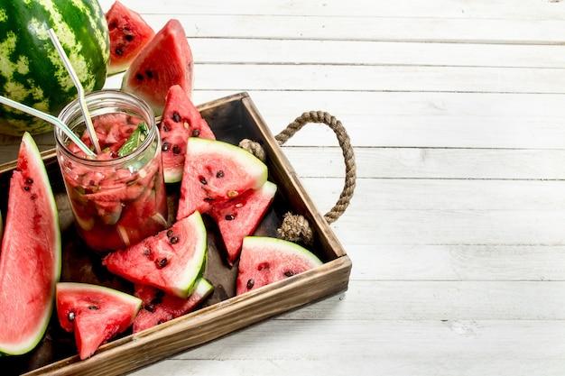 Wassermelonensaft im glas auf tablett mit wassermelonenscheiben auf weißem holztisch.