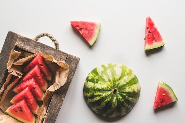 Wassermelonensaft in der holzkiste auf einem weißen hintergrund mit scheiben der wassermelone. auf einem weißen holztisch.