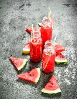 Wassermelonensaft in flaschen mit strohhalmen auf rustikalem tisch.