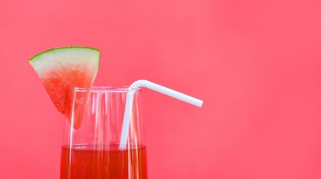 Wassermelonensaftsommer mit stückwassermelonenfrucht auf glas auf rotem hintergrund