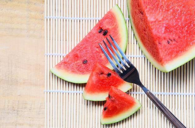 Wassermelonenscheibe auf hölzerner platte mit einer gabelfrucht