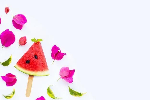 Wassermelonenscheibe eis am stiel mit bougainvillea-blume auf weiß on