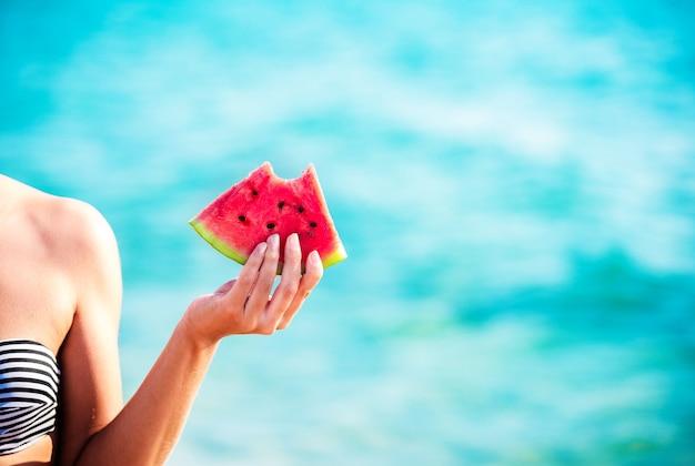 Wassermelonenscheibe in frauenhand über meer
