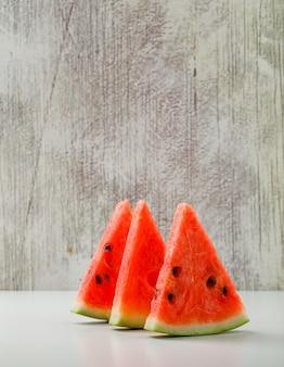 Wassermelonenscheiben auf weiß- und schmutzhintergrund. seitenansicht.