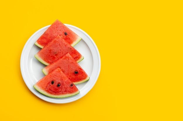 Wassermelonenscheiben auf weißem teller auf gelber oberfläche