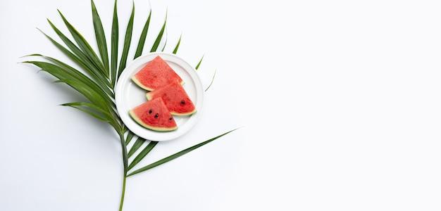 Wassermelonenscheiben auf weißem teller mit grünen blättern auf weißem hintergrund.