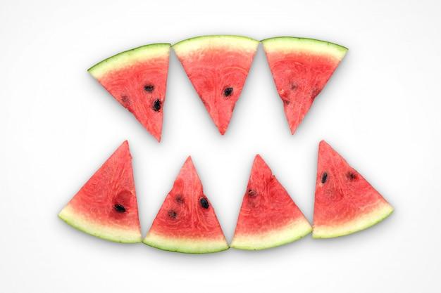Wassermelonenscheiben, die wie zähne eines dämons auf weißem hintergrund angeordnet werden, genießen zu essen