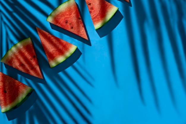 Wassermelonenscheiben draufsicht auf blauem hintergrund mit blattschatten und kopierraum