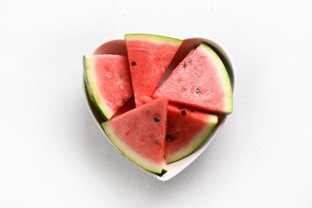 Wassermelonenscheiben in platte als herz auf weißem hintergrund. flach liegen. leckeres dessertessen.