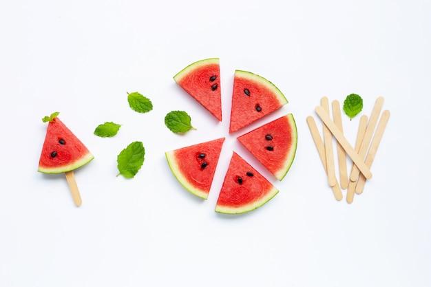 Wassermelonenscheiben mit eis am stiel auf weiß