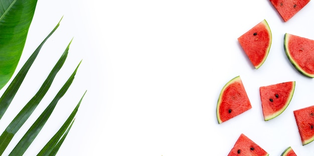 Wassermelonenscheiben mit grünen blättern auf weißem hintergrund. ansicht von oben