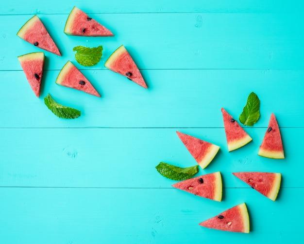 Wassermelonenscheiben mit tadellosen blättern auf blauer tabelle