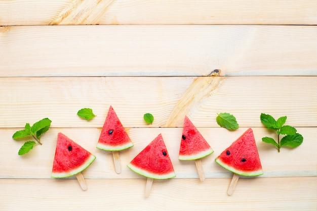 Wassermelonenscheibeneis am stiel auf braunem holz