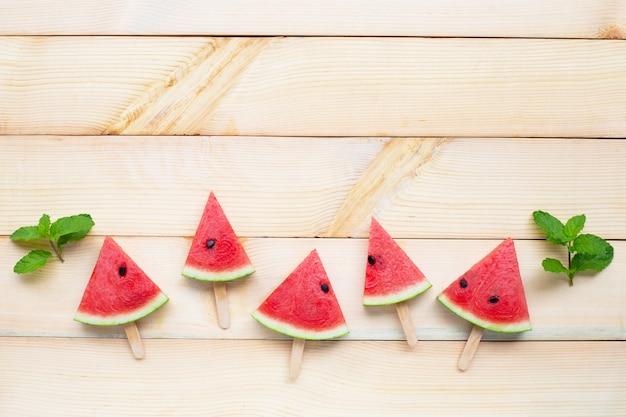 Wassermelonenscheibeneis am stiel auf hölzernem hintergrund