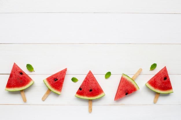 Wassermelonenscheibeneis am stiel auf weißem hölzernem hintergrund. copyspace
