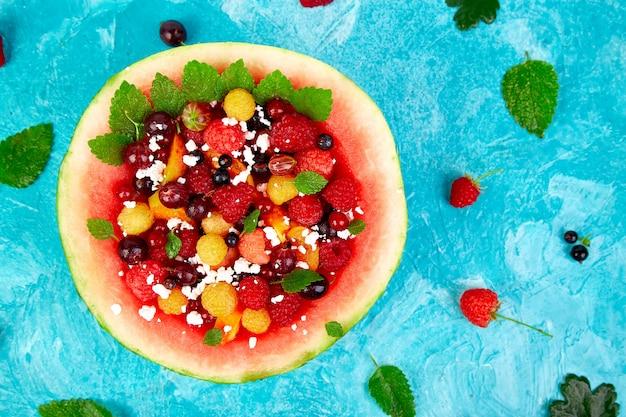 Wassermelonenschüssel mit hüttenkäse und beeren