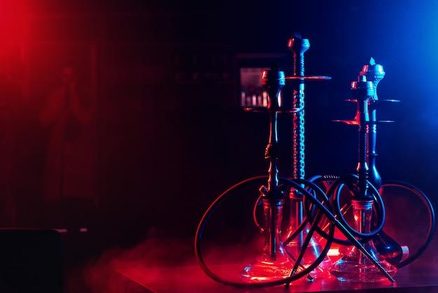 Wasserpfeifen mit shisha-kohlen in schalen vor einem rauchhintergrund mit neonbeleuchtung in einem restaurant mit einem kopierraum