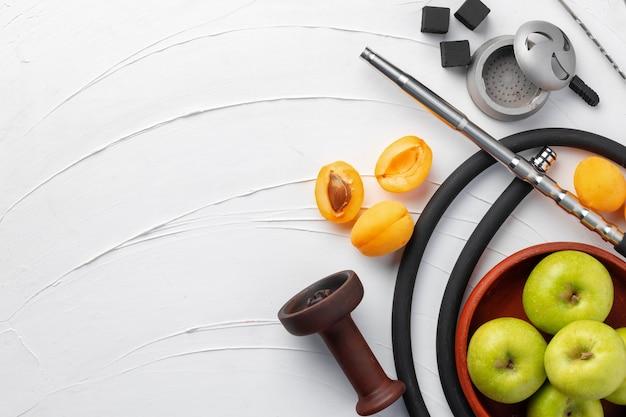 Wasserpfeifenteile mit frischen aprikosen auf dem tisch