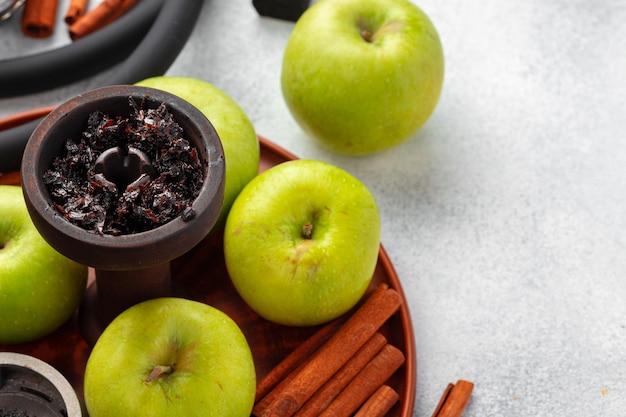 Wasserpfeifenteile mit grünen äpfeln auf tischnahaufnahme