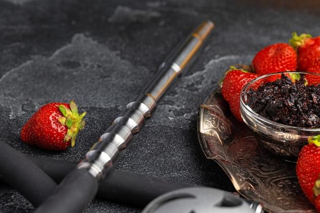 Wasserpfeifenteile und erdbeere auf grauer oberfläche schließen foto oben