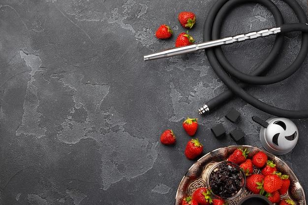 Wasserpfeifenteile und erdbeere auf grauer oberfläche schließen