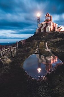 Wasserpfütze auf rasenfläche nahe einem leuchtturm