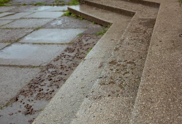 Wasserpfützen auf den betonplatten und treppen auf der straße nach dem regen