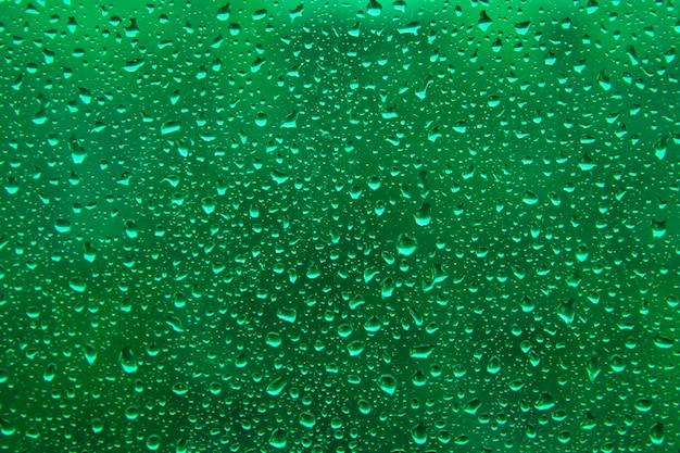 Wasserregentropfen auf saurer grüner oberfläche als hintergrund. abstrakter hintergrund.
