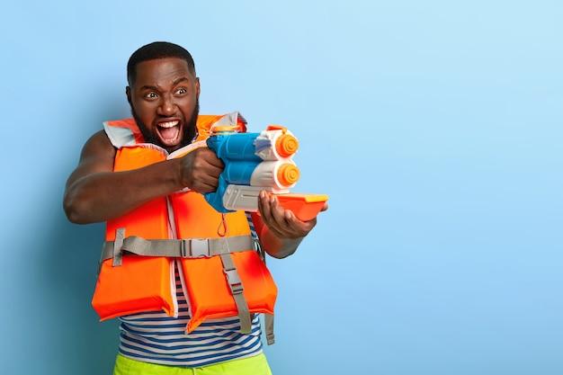 Wasserschlacht. emotionaler schwarzer mann schreit ich werde dich erschießen, hält spielzeug wasserpistole