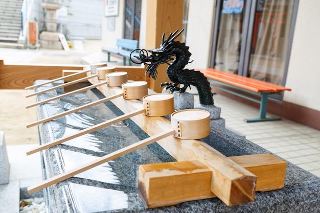 Wasserschöpflöffel aus holz und teich vor dem shinto-schrein zum händewaschen und gurgeln vor dem betreten des schreins.