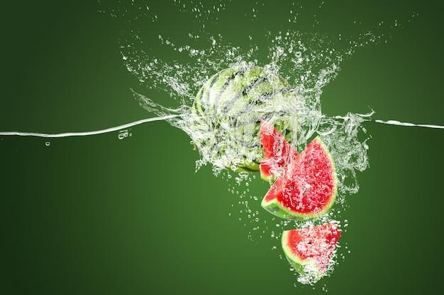 Wasserspritzen auf scheibe wassermelone unter wasser auf einem grünen hintergrund