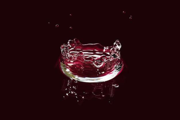 Wasserspritzer isoliert auf dunkelrot. frisches sauberes transparentes trinkwasserspritzen.
