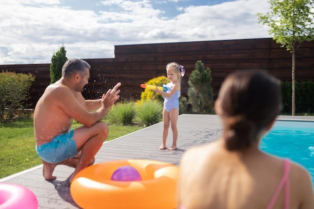 Wasserstrahl verwenden. mädchen, das einen schönen badeanzug mit wasserblaster trägt, während sie spaß mit den eltern in der nähe des pools hat