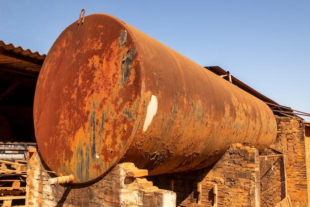 Wassertank mit allem rostigen metall mit blauem himmel im hintergrund