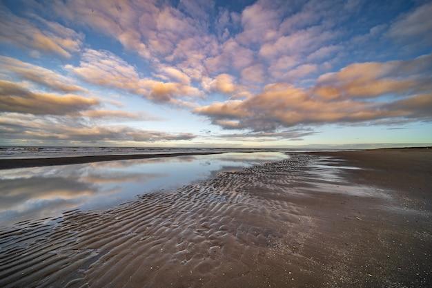Wasserteich an der küste unter einem blauen bewölkten himmel