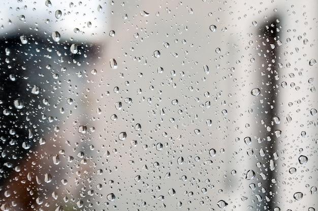 Wassertropfen auf dem fensterglas vor einem verschwommenen hintergrund an einem bewölkten regnerischen tag