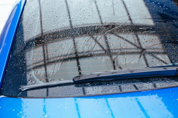 Wassertropfen auf der heckscheibe des autos. autowaschkonzept