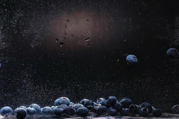 Wassertropfen auf reife süße blaubeere. frischer blaubeerhintergrund mit kopienraum für ihren text. veganes und vegetarisches konzept. makrobeschaffenheit von blaubeerbeeren.