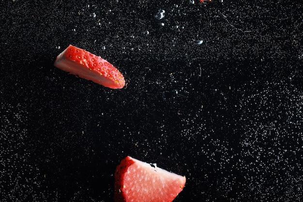 Wassertropfen auf reife süße erdbeere. frischer beerenhintergrund mit kopienraum für ihren text. veganes lebensmittelkonzept.