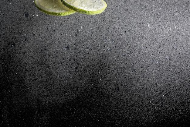 Wassertropfen auf reife süße zitrone. frischer kalkhintergrund mit kopienraum für ihren text. veganes und vegetarisches konzept.