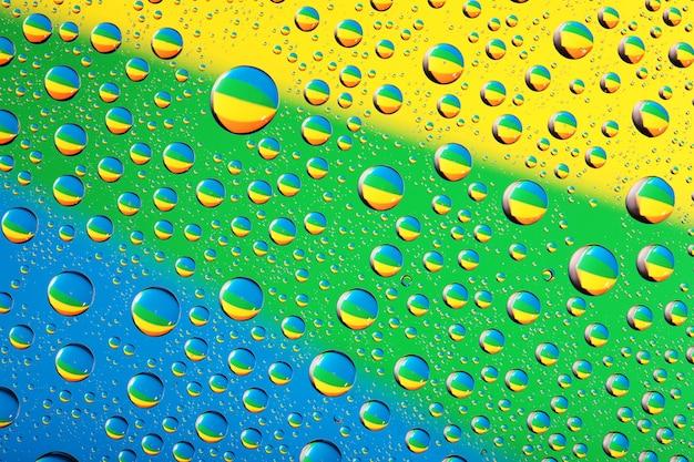 Wassertropfen-hintergrund auf blauen, gelben und grünen farben