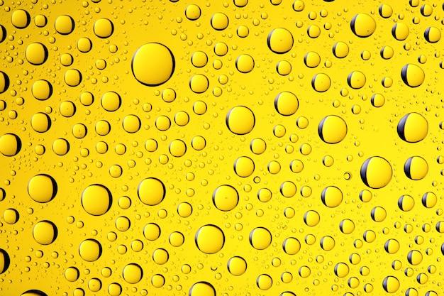 Wassertropfen-hintergrund auf gelber farbe